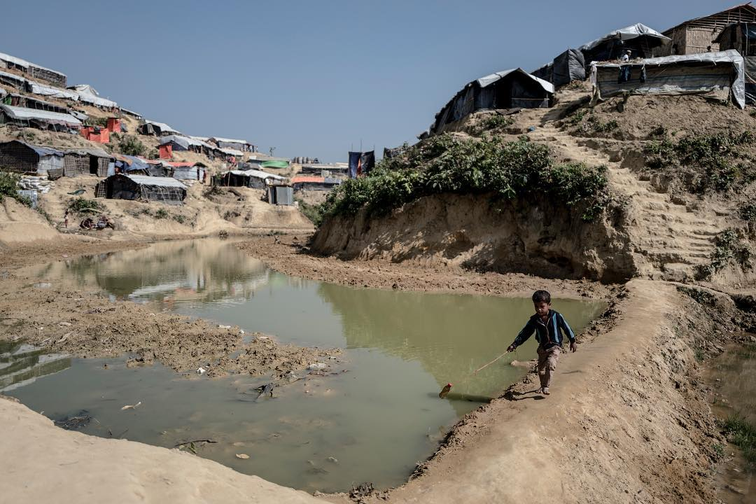 A Rohingyan child plays in the muddy pits at Kutupalong refugee camp