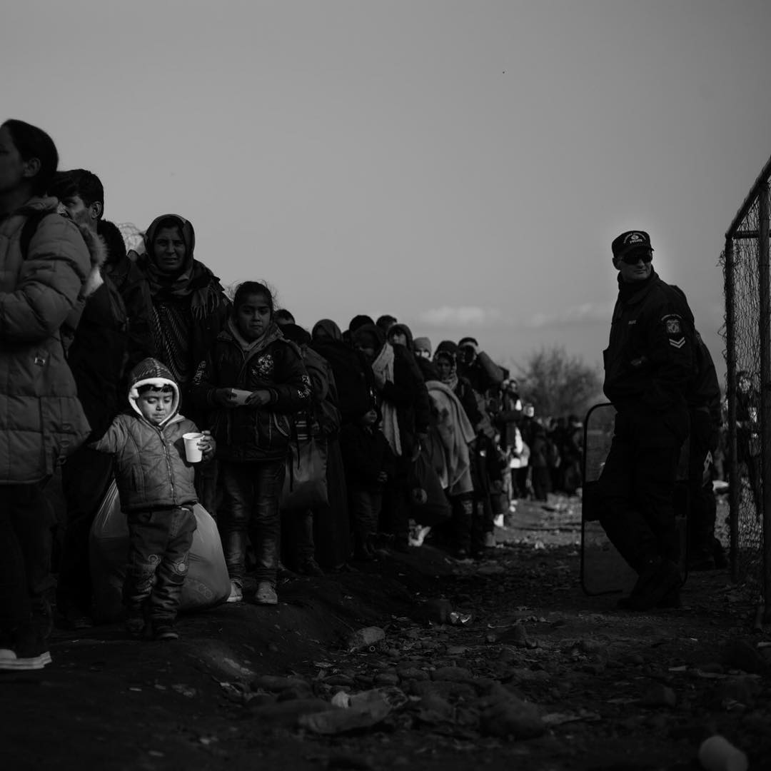 A Young Afghan boy stands in line at The border to Macedonia