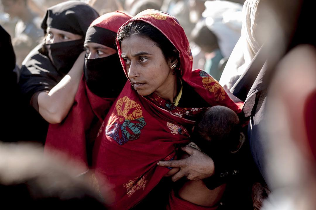 A Rohingyan woman protects her child and her spot as fighting breaks out in the que for life vital aid delivery. Kutupalong Refugeecamp @reduxpictures