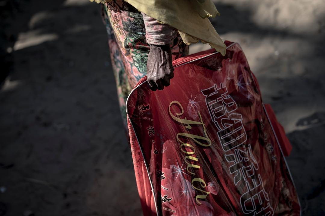 An elderly Rohingyan woman stand with all of her belongings. She arrived in Bangladesh during the Night and now awaits gettong transported to the camps
