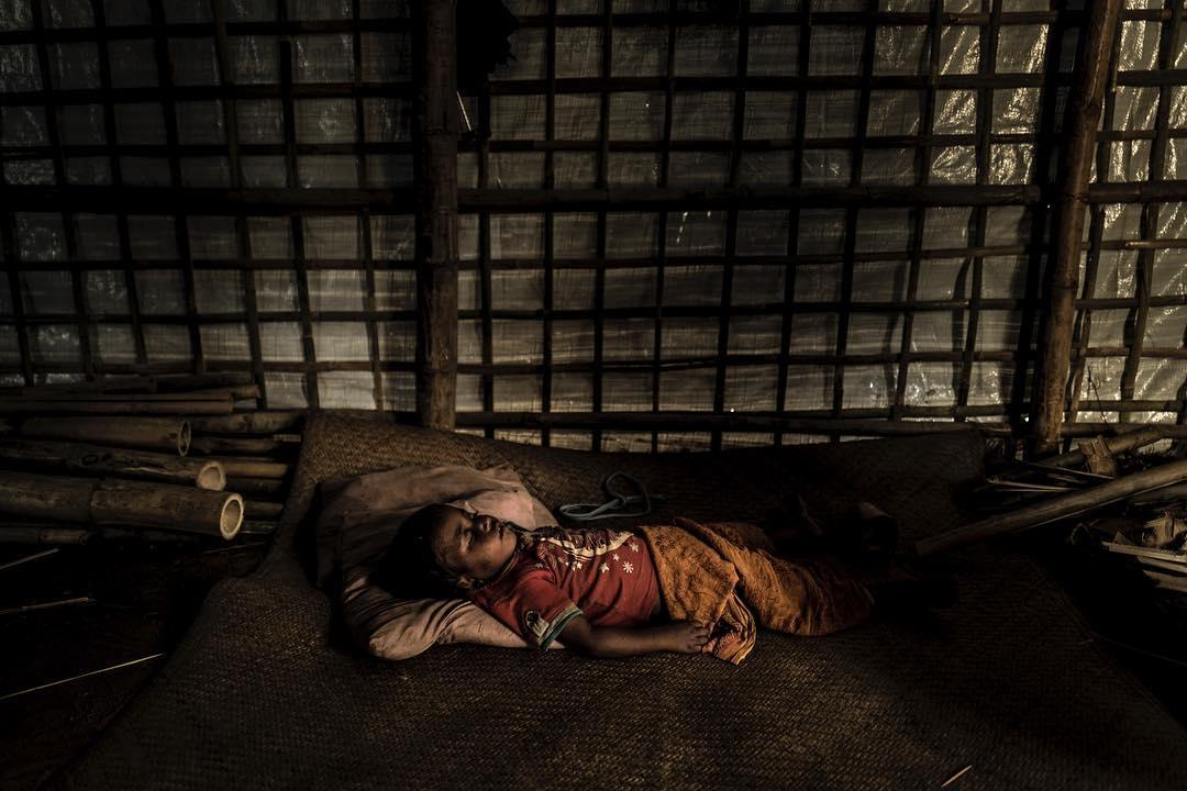 A Rohingyan girl sleeps inside her familys new makeshift shelter in Kutupalong refugeecamp