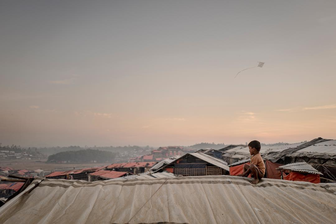 A Rohingyan boy sits ontop of a makeshift tent in Jamtoli refugee camp