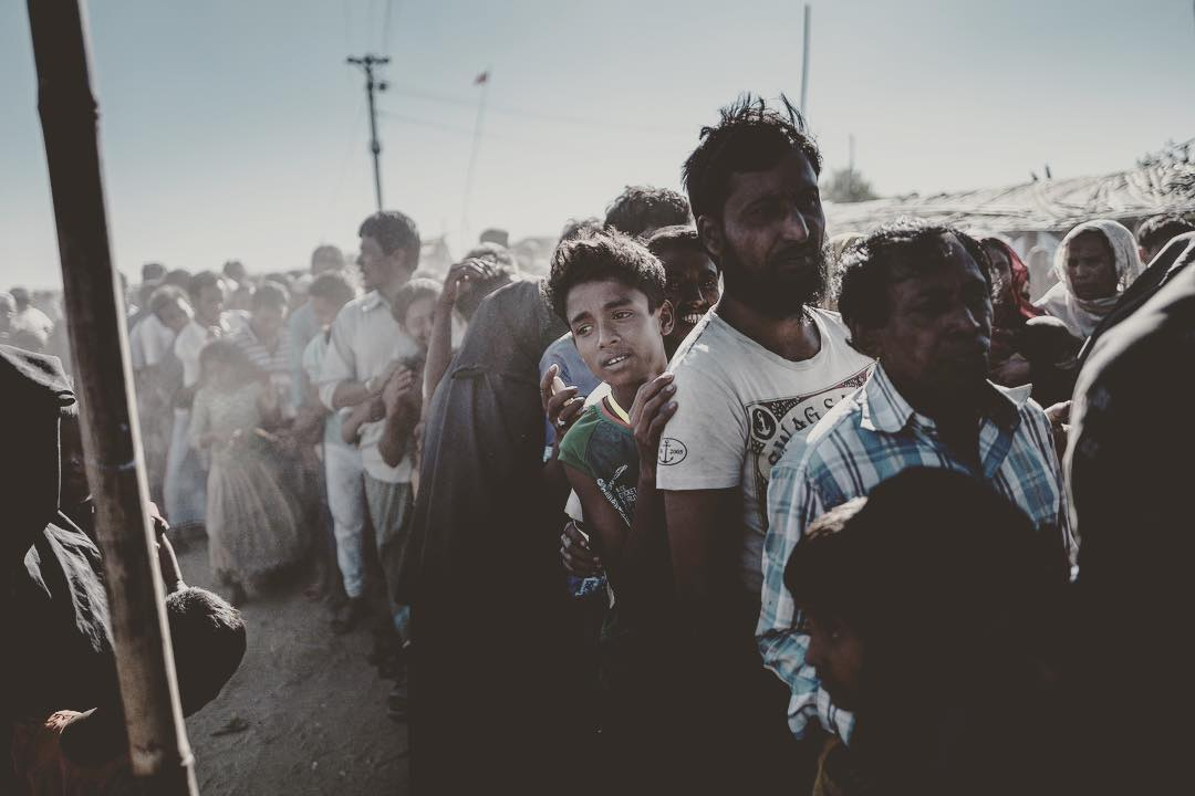 Rohingyan men stand in line for their life vital aid relief